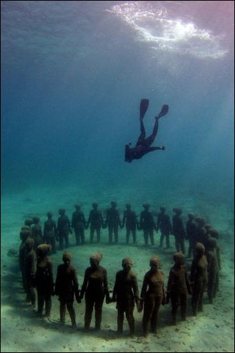 Diver inspecting underwater sculptures in Cancun